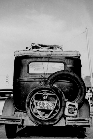 "Rear view of an ""Okie's"" Car heading West as part of the ""Dust Bowl"" migration of American farmers (1941) NARA-Image, ID=532820. Public Domain."